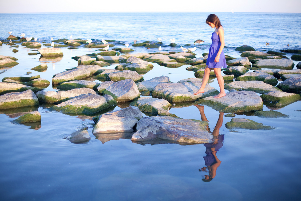 Toronto Adventure Photographer : girl walking on rocks at the Beaches on Lake Ontario