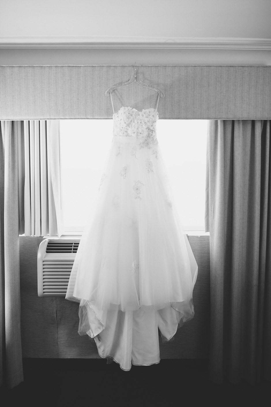 Wedding dress hanging on hangar in hotel room